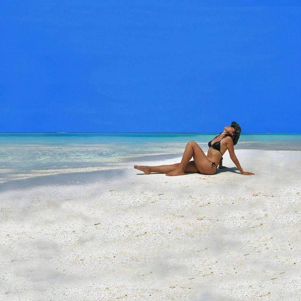 Image of woman sunbathing on a beach in a bikini for seven deadly sins of skincare blog post