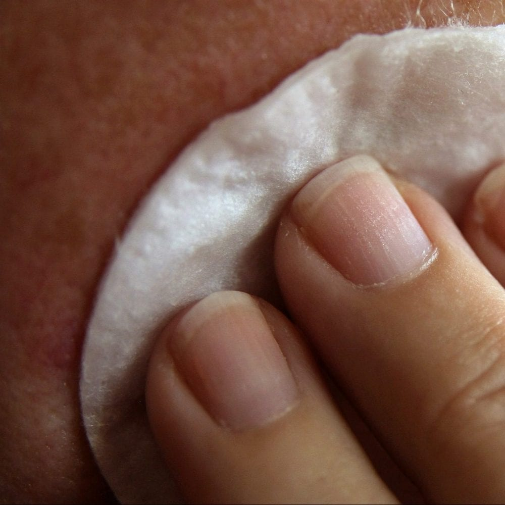 Image of woman's hand cleansing face with cotton pad for skin cleansing and toning blog post