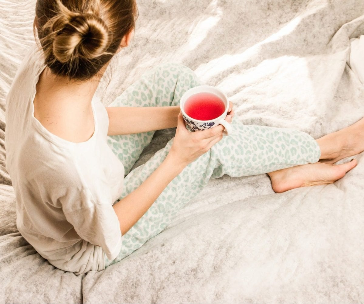 image of woman relaxing on a bed with cup of tea for sunday vibes beauty digest